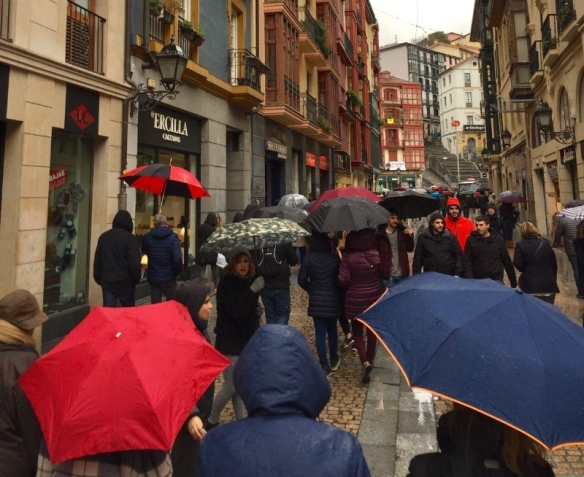 Rain in Bilbao. Locals walking with umbrella